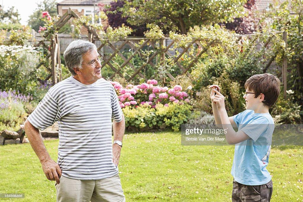 Grandson takes photo of grand dad with phone. : Stock Photo