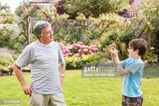 Grandson takes photo of grand dad with phone. : Foto de stock