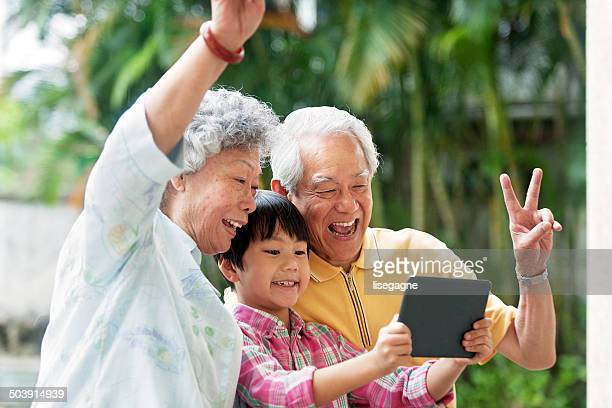 Grandson teaching grandparents how to use a digital tablet