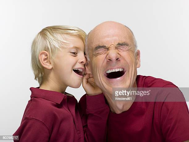 Grandson (8-9) whispering to grandfather, close-up