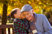 Grandson whispering to happy grandfather sitting at park during autumn