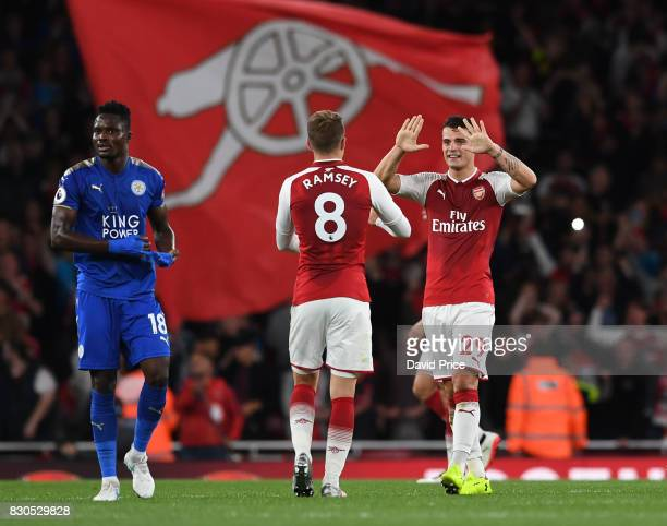 Granit Xhaka and Aaron Ramsey of Arsenal celebrate at the final whistle during the Premier League match between Arsenal and Leicester City at...