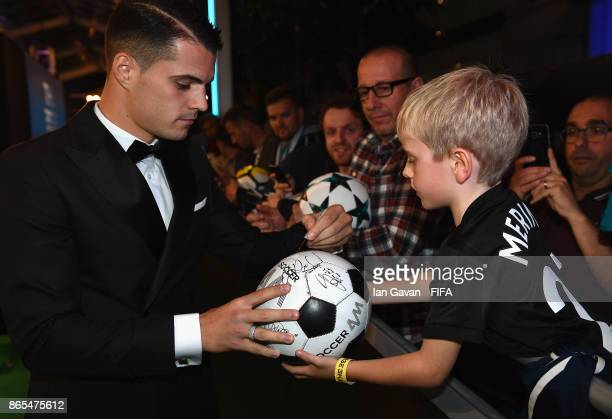 Granit Xhaka arrives and writes autographs on the green carpet for The Best FIFA Football Awards at The London Palladium on October 23 2017 in London...