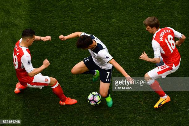 Granit Xhaka of Arsenal and Nacho Monreal of Arsenal attempt to tackle HeungMin Son of Tottenham Hotspur during the Premier League match between...