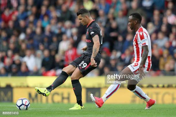 Granit Xhaka of Arsenal and Saido Berahino of Stoke City battle for possession during the Premier League match between Stoke City and Arsenal at...