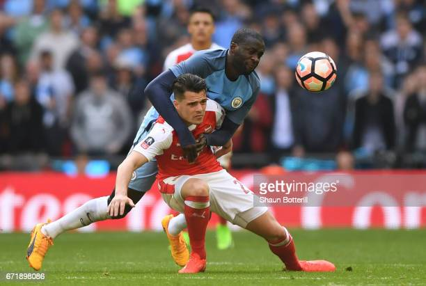 Granit Xhaka of Arsenal and Yaya Toure of Manchester City compete for the ball during the Emirates FA Cup SemiFinal match between Arsenal and...