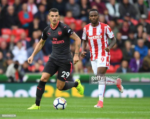 Granit Xhaka of Arsenal breaks past Saido Berahino of Stoke during the Premier League match between Stoke City and Arsenal at Bet365 Stadium on...