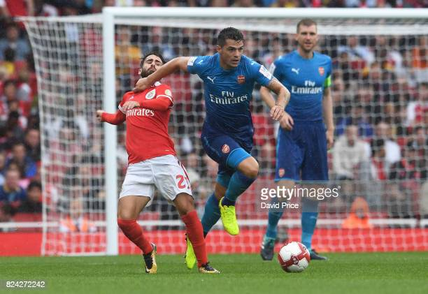 Granit Xhaka of Arsenal bursts past Franco Cervi of Befica during the match between Arsenal and SL Benfica at Emirates Stadium on July 29 2017 in...