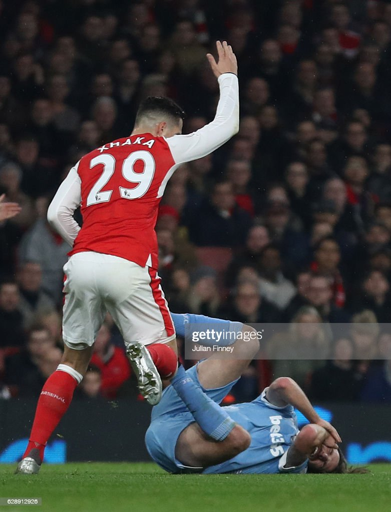 Granit Xhaka of Arsenal (L) reacts to Joe Allen of Stoke City (R) going down after being challenged by Shkodran Mustafi of Arsenal (not pictured) during the Premier League match between Arsenal and Stoke City at the Emirates Stadium on December 10, 2016 in London, England.