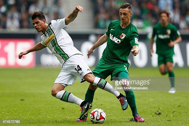 Granit Xhaka of Borussia Moenchengladbach and Dominik Kohr of FC Augsburg battle for the ball during the Bundesliga match between Borussia...