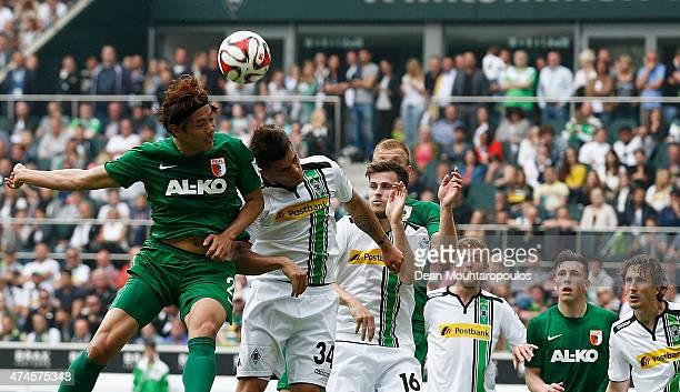 Granit Xhaka of Borussia Moenchengladbach and Hong JeongHo of FC Augsburg battle for the header during the Bundesliga match between Borussia...