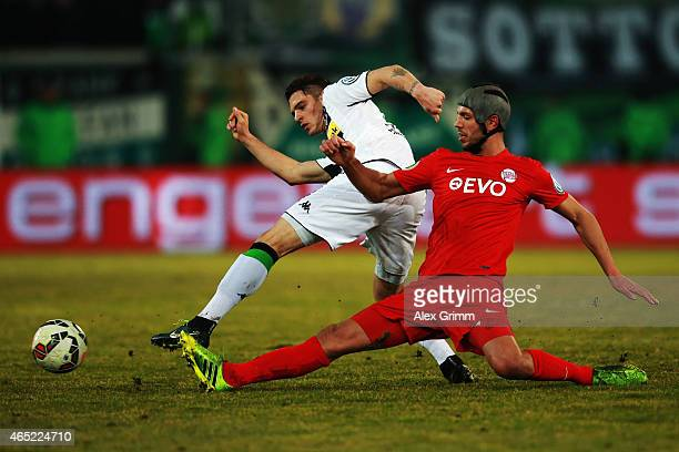 Granit Xhaka of Moenchengladbach is challenged by Klaus Gjasula of Offenbach during the DFB Cup Round of 16 match between Kickers Offenbach and...