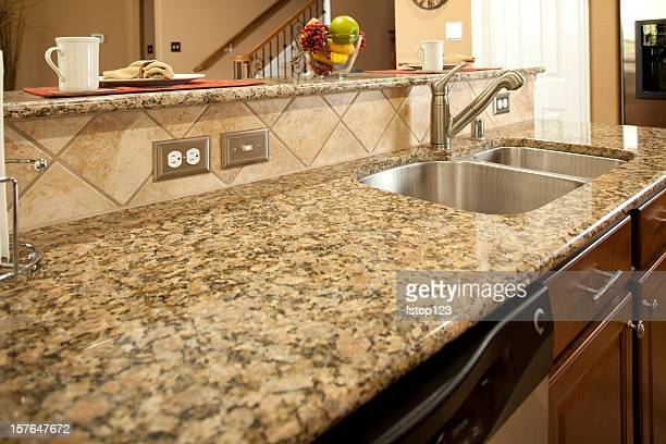 Granite kitchen counter with dishwasher underneath. Sink. Bar.