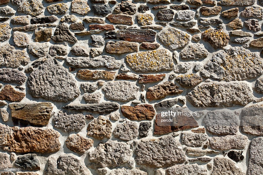 Granite stone wall in the sunlight, full frame. : Stock Photo
