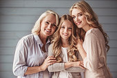Beautiful women generation: granny, mom and daughter are hugging, looking at camera and smiling