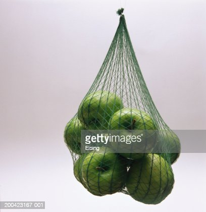 Granny Smith apples hanging in a net