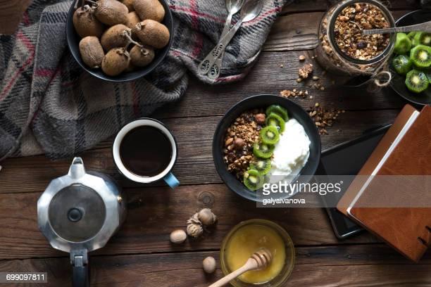 Granola, kiwi fruit and yogurt with coffee