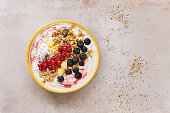 Granola with fresh fruits, chia and sesame seeds served in a bowl on concrete background.  Top view, blank space