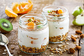 Granola with yogurt and fruits in a rustic jar. Delicious healthy American food for breakfast. Traditional US snack. Close-up shot.