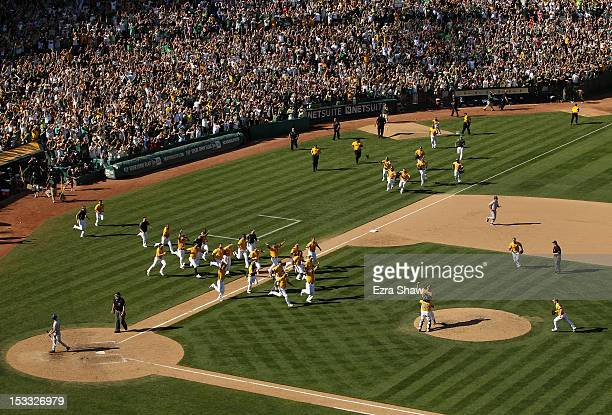 Grant Balfour and Derek Norris celebrate with the rest of the Oakland Athletics after they beat the Texas Rangers to win the American League West...