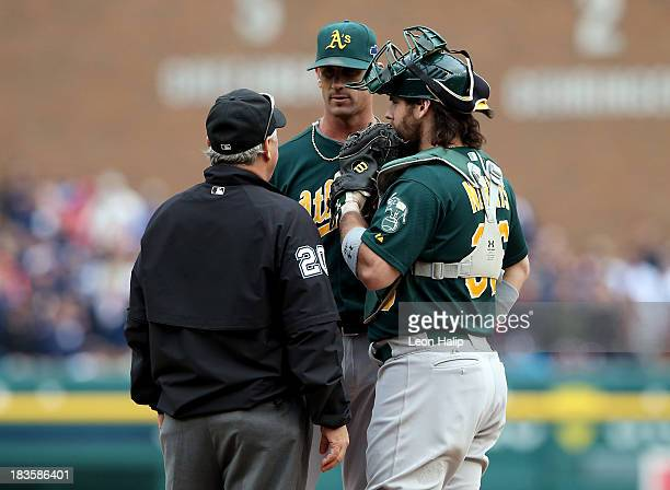 Grant Balfour and Derek Norris of the Oakland Athletics speak with second base umpire Tom Hallion in the ninth inning during Game Three of the...