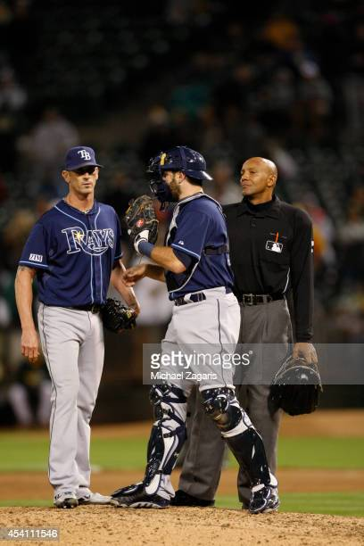 Grant Balfour and Jose Molina of the Tampa Bay Rays talk on the mound as Umpire C B Bucknor hurries them up during the game against the Oakland...