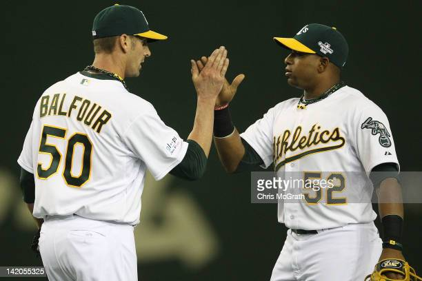 Grant Balfour of the Oakland Athletics celebrates victory with team mate Yoenis Cespedes during the MLB Opening Series game two between the Seattle...