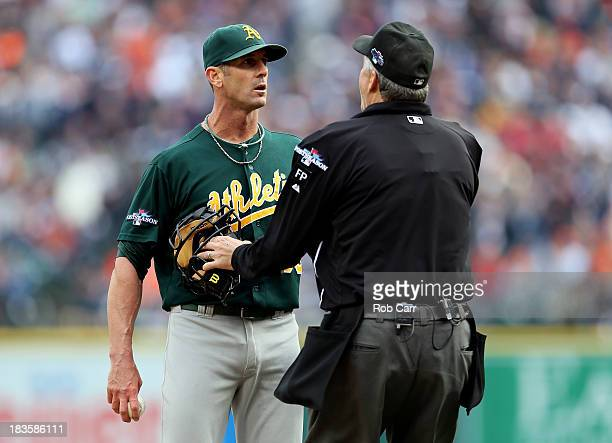 Grant Balfour of the Oakland Athletics is held back by home plate umpire Gary Darling after exchanging words with Victor Martinez of the Detroit...