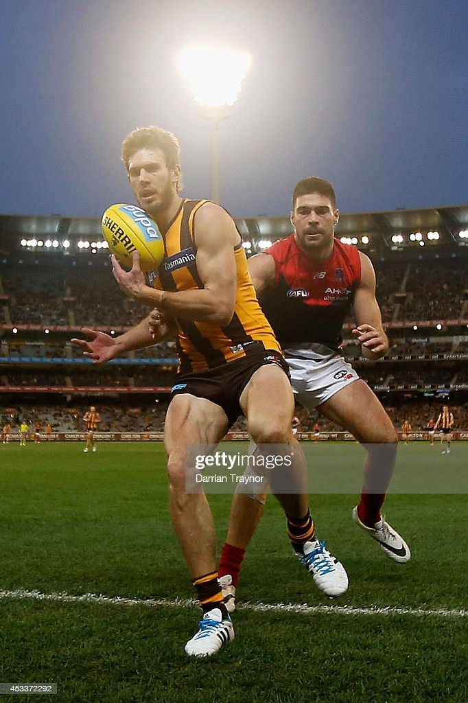 Grant Birchall of the Hawks is pushed out of bounds by Chris Dawes of the Demons during the round 20 AFL match between the Hawthorn Hawks and the Melbourne Demons at Melbourne Cricket Ground on August 9, 2014 in Melbourne, Australia.