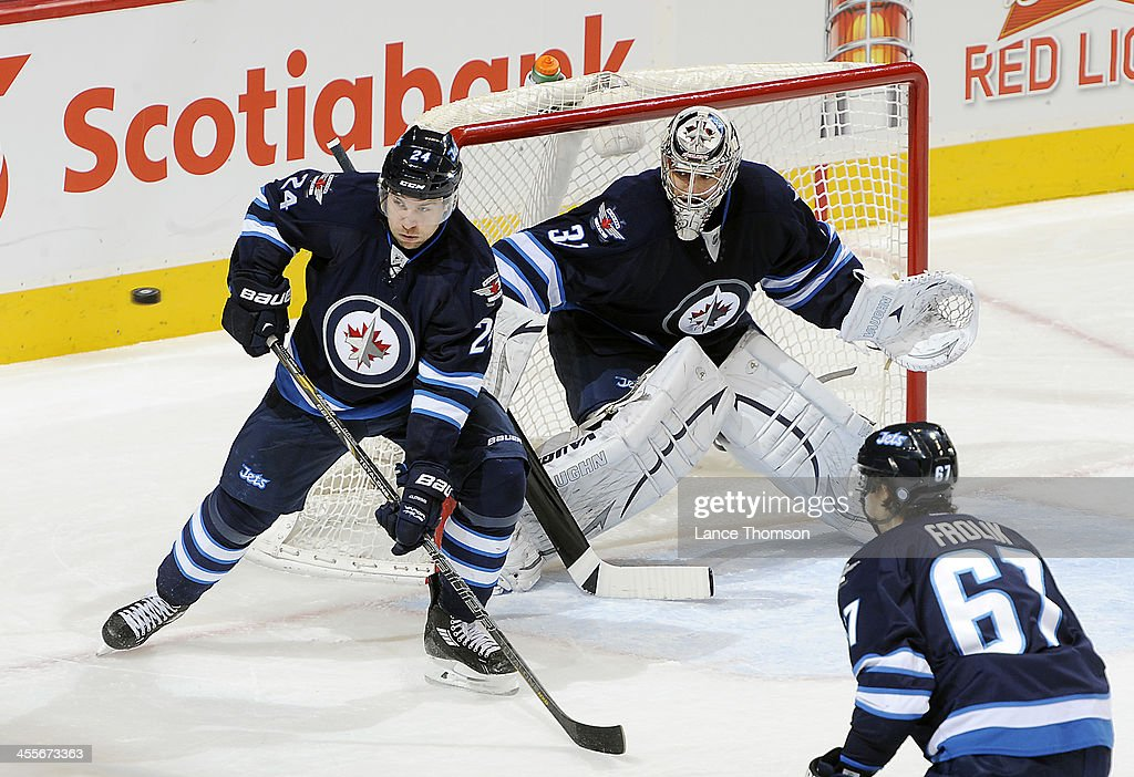 Grant Clitsome goaltender Ondrej Pavelec and Michael Frolik of the Winnipeg Jets watch as the puck flies towards the net during second period action...