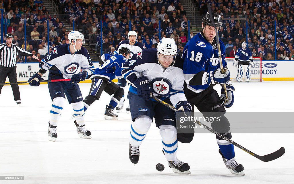 Grant Clitsome #24 of the Winnipeg Jets battles <a gi-track='captionPersonalityLinkClicked' href=/galleries/search?phrase=Adam+Hall&family=editorial&specificpeople=202919 ng-click='$event.stopPropagation()'>Adam Hall</a> #18 of the Tampa Bay Lightning for the puck during the second period of the game at the Tampa Bay Times Forum on February 1, 2013 in Tampa, Florida.