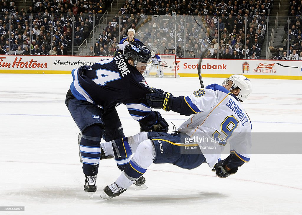Grant Clitsome of the Winnipeg Jets lays out Jaden Schwartz of the St Louis Blues during third period action at the MTS Centre on December 10 2013 in...