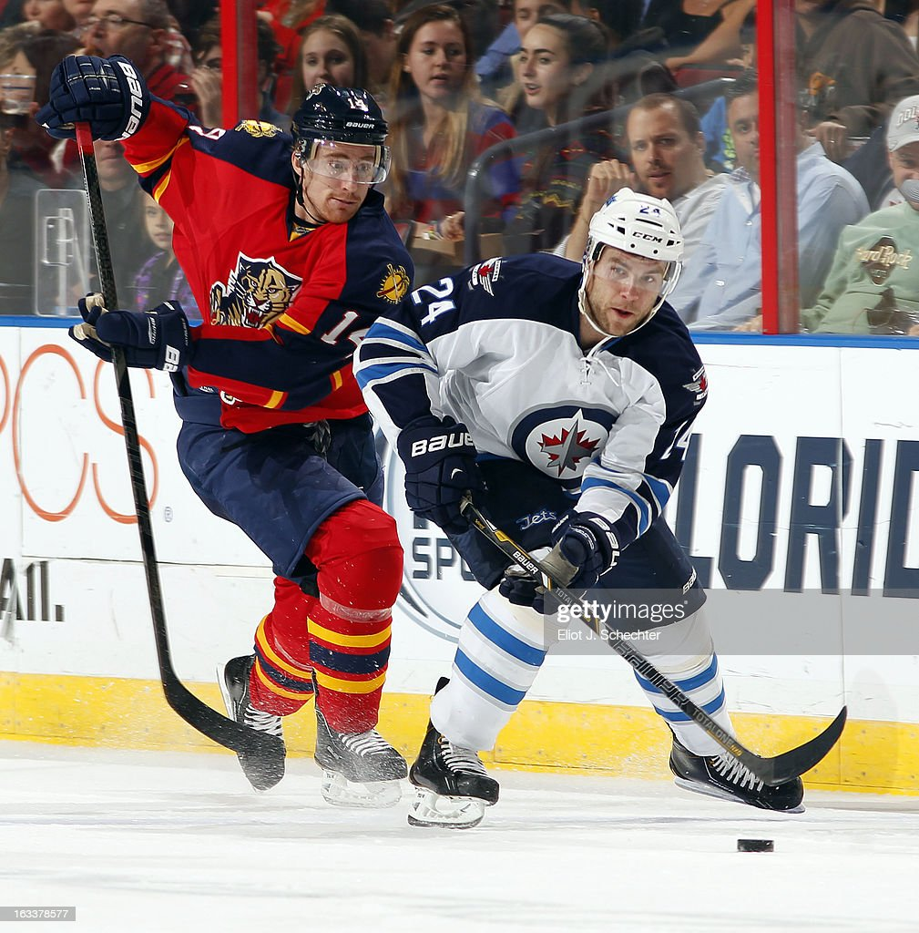 Grant Clitsome #24 of the Winnipeg Jets skates with the puck against Tomas Fleischmann #14 of the Florida Panthers at the BB&T Center on March 8, 2013 in Sunrise, Florida.