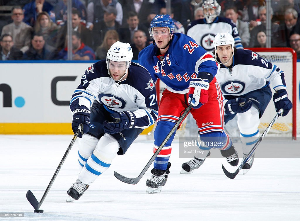 Grant Clitsome #24 of the Winnipeg Jets skates with the puck under pressure by Ryan Callahan #24 of the New York Rangers in the second period at Madison Square Garden on February 26, 2013 in New York City.