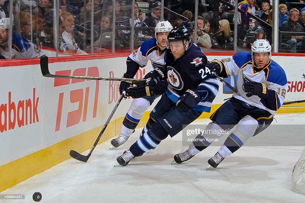 Grant Clitsome of the Winnipeg Jets tries to outrace Patrik Berglund and Derek Roy of the St Louis Blues to the loose puck during first period action...