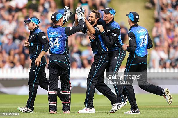 Grant Elliott of New Zealand celebrates with Luke Ronchi and Martin Guptill after taking the wicket of Sohaib Maqsood of Pakistan during the One Day...