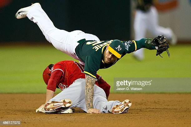 Grant Green of the Los Angeles Angels of Anaheim is tagged out attempting to steal second base by Brett Lawrie of the Oakland Athletics during the...