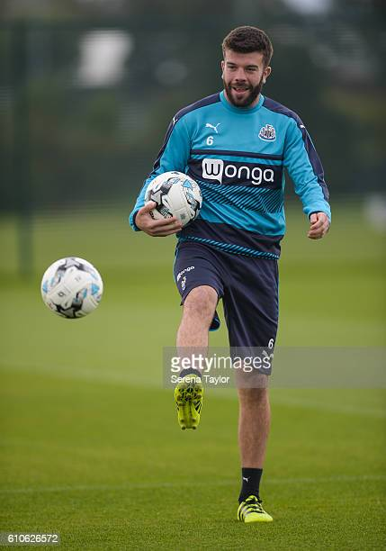 Grant Hanley kicks the ball whilst holding a second ball in his right hand during the Newcastle United Training Session at The Newcastle United...