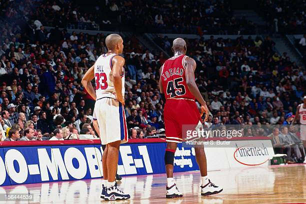 Grant Hill of the Detroit Pistons stands with Michael Jordan of the Chicago Bulls during a game circa 1995 at the Palace of Auburn Hills in Auburn...