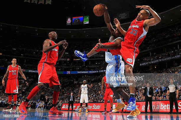 Grant Hill of the Los Angeles Clippers and Kenneth Faried of the Denver Nuggets collide as they vie for a rebound as Lamar Odom of the Los Angeles...