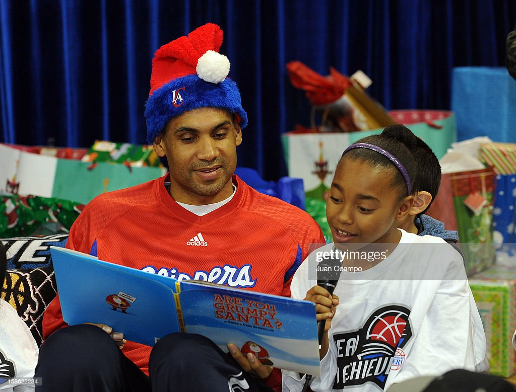 Grant Hill #33 of the Los Angeles Clippers listens as a child reads from a book during the Clippers' 'Season of Giving' Adopt a Family event on December 20, 2012 at Salvation Army Seimon Family Youth & Community Center in Los Angeles, California.