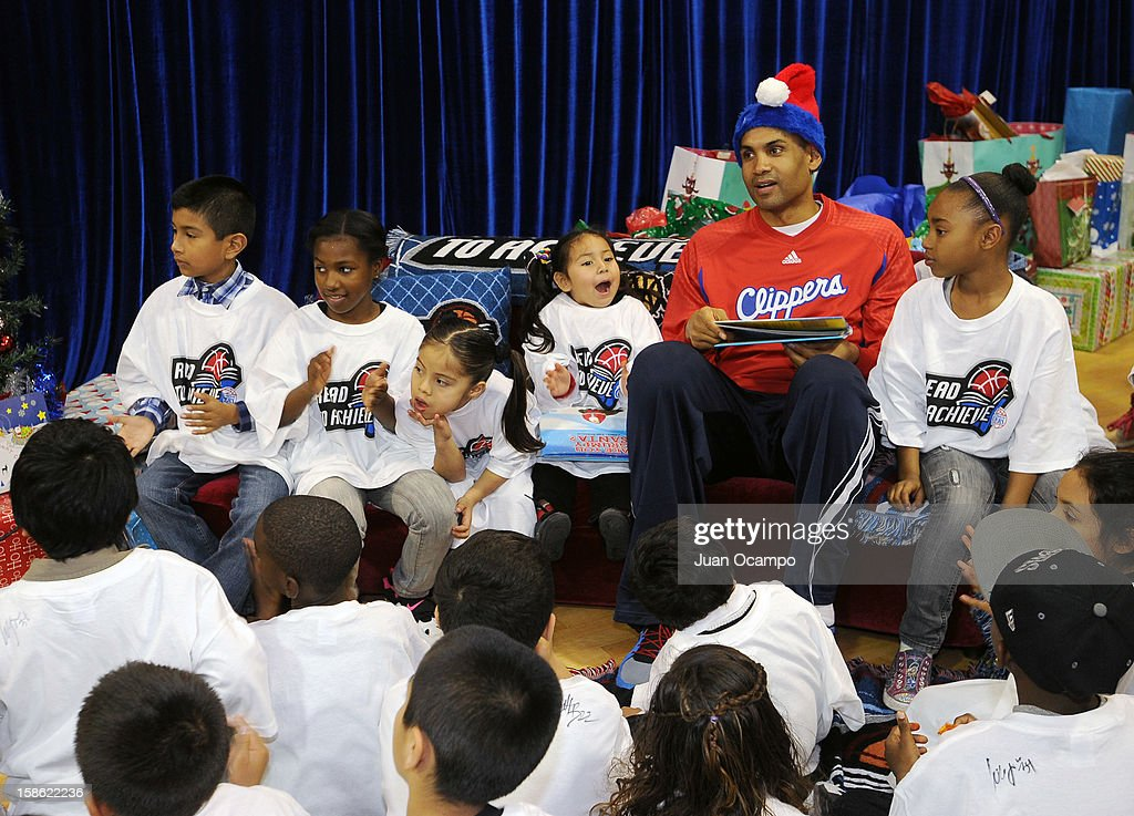 Grant Hill #33 of the Los Angeles Clippers reads to the kids during the Clippers' 'Season of Giving' Adopt a Family event on December 20, 2012 at Salvation Army Seimon Family Youth & Community Center in Los Angeles, California.
