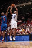 Grant Hill of the Orlando Magic takes a jump shot over Chauncey Billups of the Detroit Pistons during the game at TD Waterhouse Centre on December 25...