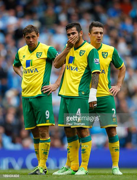 Grant Holt Bradley Johnson and Russell Martin of Norwich watch on during the Barclays Premier League match between Manchester City and Norwich City...