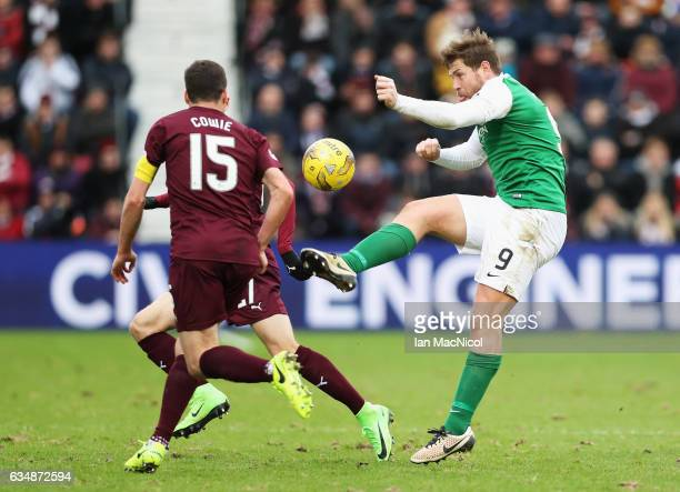 Grant Holt of Hibernian clears the ball as Don Cowie of Hearts closes in during the Scottish Cup fifth round match between Heart of Midlothian and...