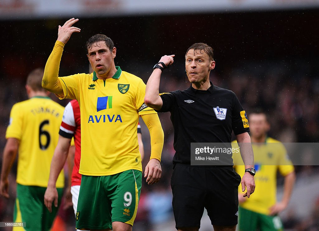 Grant Holt of Norwich City and referee Mike Jones react during the Barclays Premier League match between Arsenal and Norwich City at Emirates Stadium on April 13, 2013 in London, England.