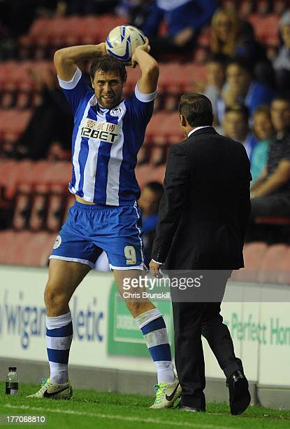 Grant Holt of Wigan Athletic clashes with Doncaster Rovers manager Paul Dickov on the touchline during the Sky Bet Championship match between Wigan...