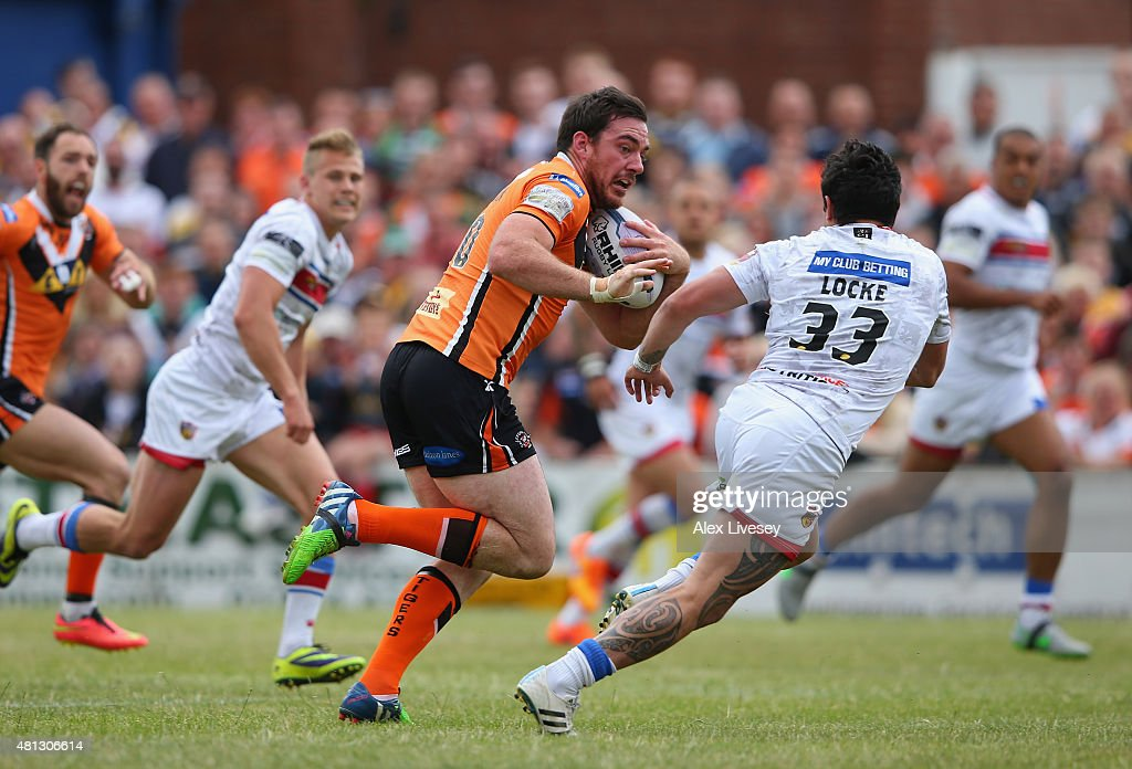 Grant Millington of Castleford Tigers breaks past Kevin Locke of Wakefield Trinity Wildcats on his way to scoring their first try during the First...