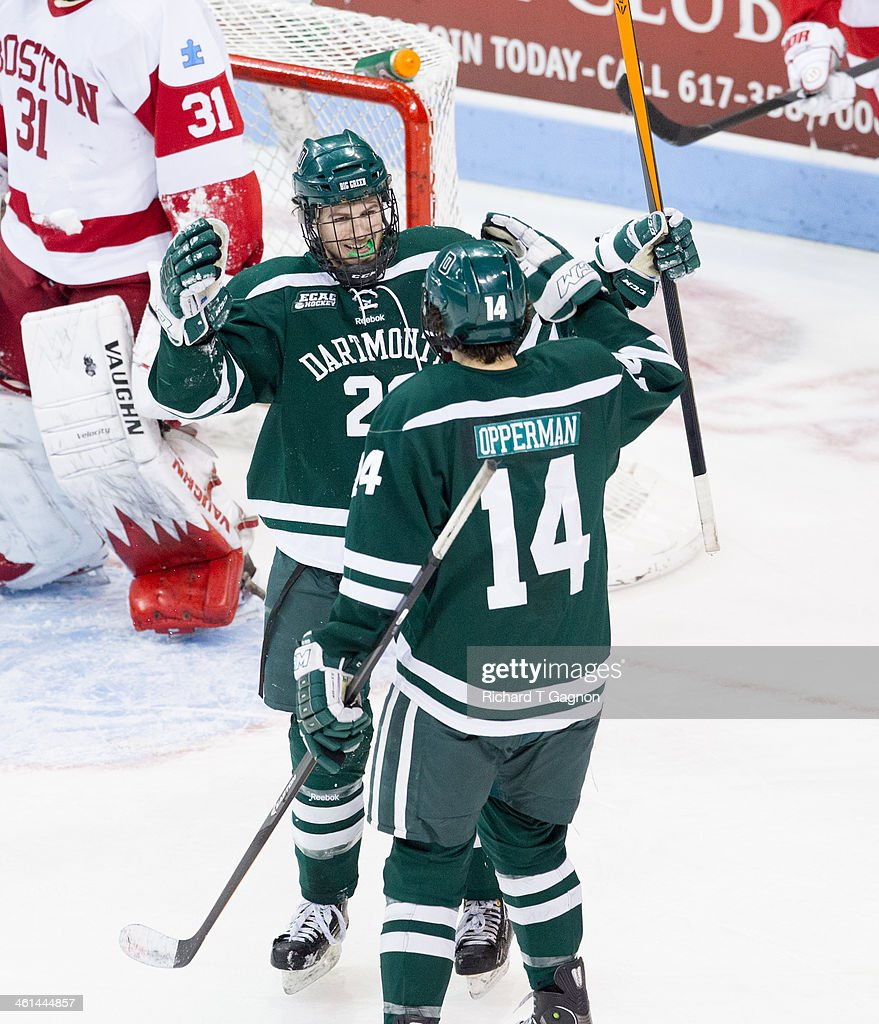 Grant Opperman #14 of the Dartmouth College Big Green and teammate Nick Bligh #23 celebrate a goal that was eventually overturned during NCAA hockey action against the Boston University Terriers at Agganis Arena on January 8, 2014 in Boston, Massachusetts.
