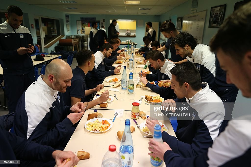 US Granville football club's players have a dinner after a training session near the Louis Dior stadium on February 8, 2016 in Granville, northwestern France. / AFP / CHARLY TRIBALLEAU